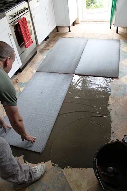 Adhesive goes down and insulation boards that work with the underfloor heating are set.