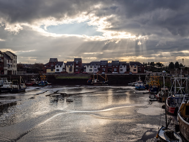 Photo of sun breaking through the clouds over Maryport harbour on Monday