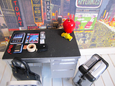 Modern dolls' house miniature desk with a selection of travel necessities arranged on it, including a tablet, guide books, digital camera, passport, glasses and a roll of duct tape.