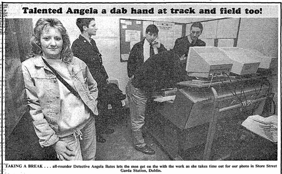 Relaxed blonde woman in casual clothes with four policemen working on computers behind her