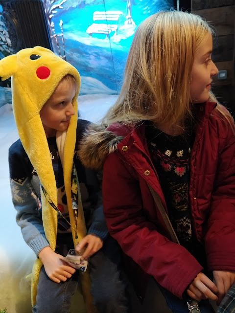 children at christmas grotto, one wears pikachu hat