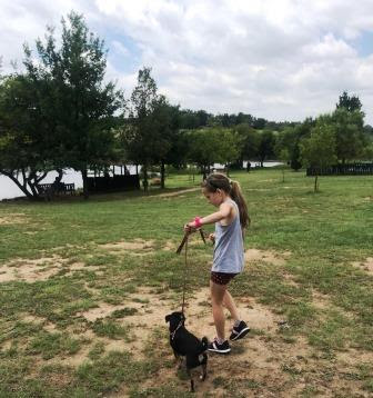 Girl walking with dog at dog park
