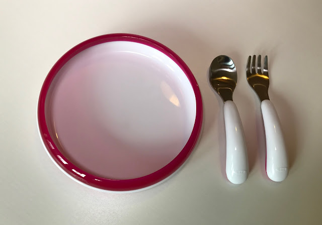 The white plate with training ring attached next to the fork and spoon