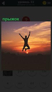 В свете заката мужчина совершает прыжок вверх, подняв руки