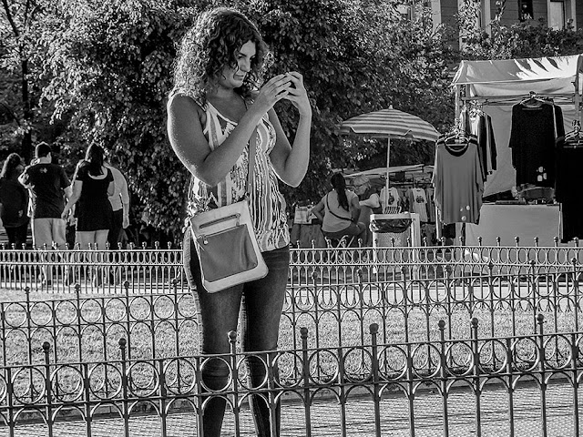 Joven sola con celular en una soleada tarde.