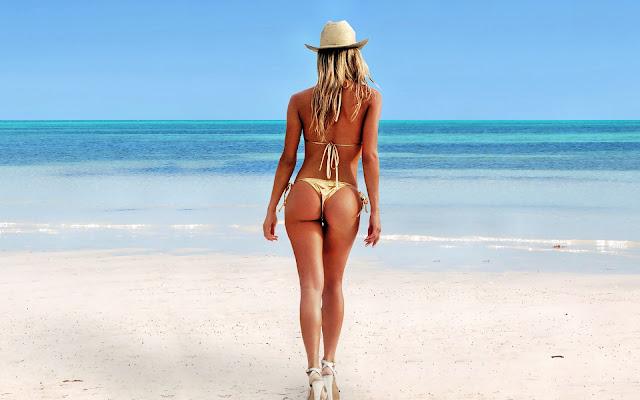 Vrouw in bikini stapt de zee in