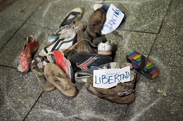 """Zapatillas y zapatos rotos con un cartel que dice """"libertad"""""""