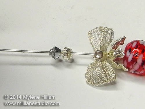 Eye pin strung with the upturned bottle bead, bow charm and findings.