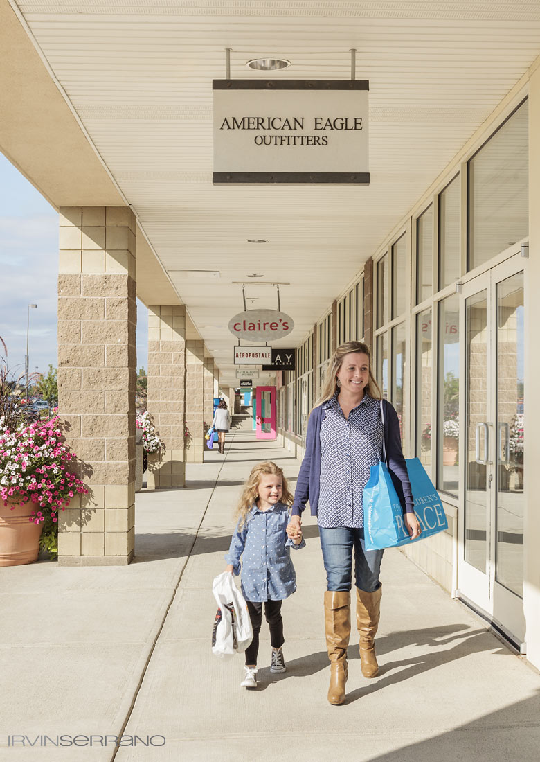A young mother and her daughter pass by American Eagle Outfitters as they shop an open air strip mall in Augusta, Maine.