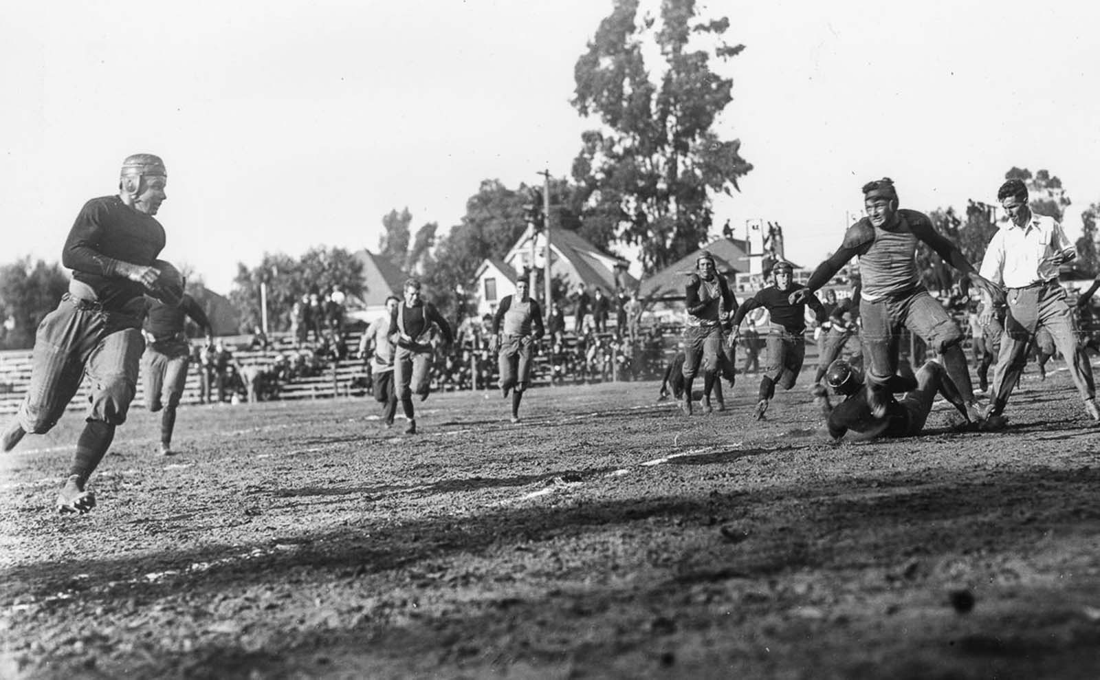 The University of Southern California Trojans football team run up field to make the play against the Saint Mary's College Gaels at the Los Angeles Memorial Coliseum. 1915.