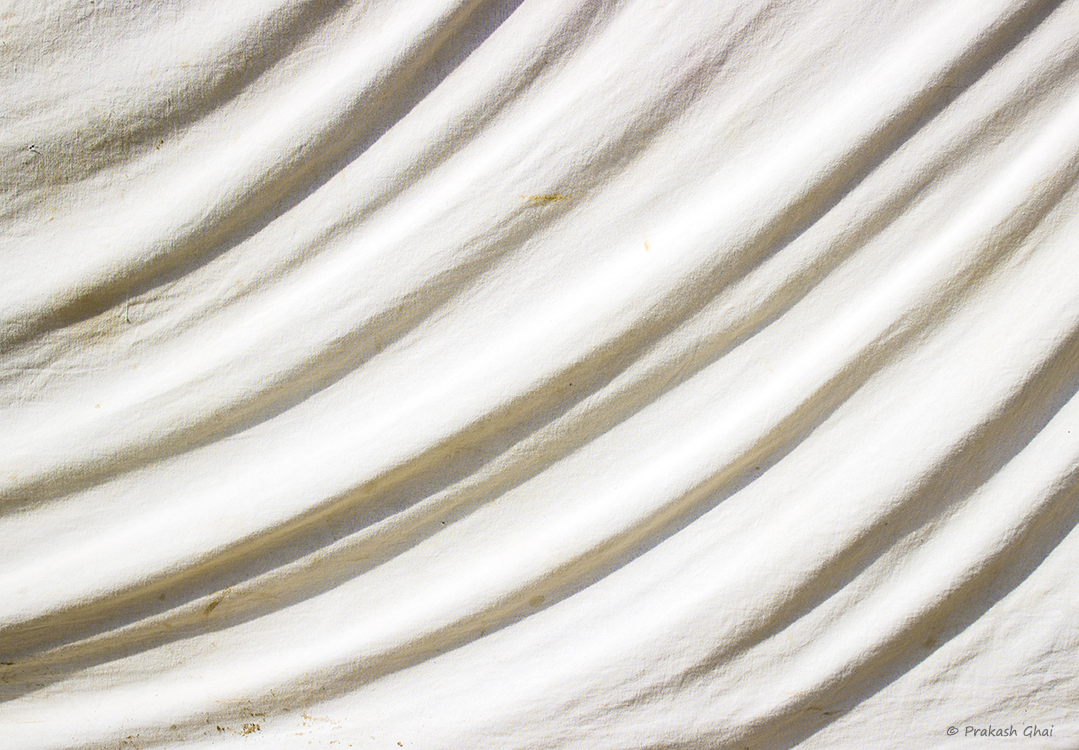 A Minimalist Photo of curves in repetition formed by light and shadow combination on a Creased white cloth