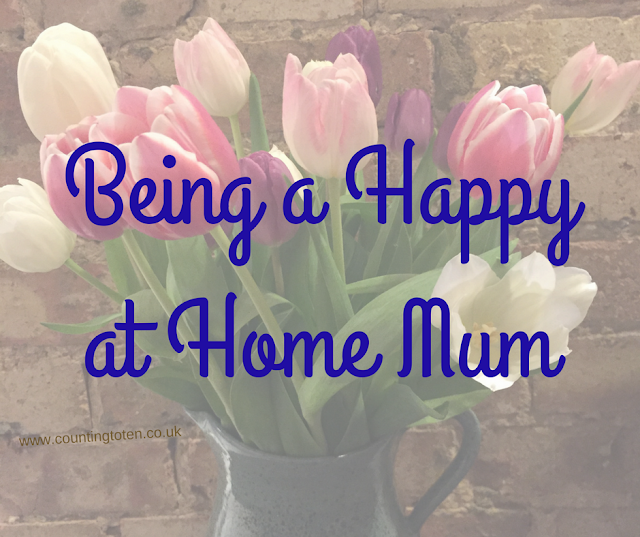 Semi transparent image of a vase of tulips in front of a brick wall with the text: being a happy at home mum in front of it