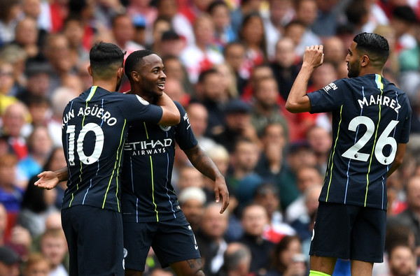Raheem Sterling of Manchester City celebrates after scoring his team's first goal with Sergio Aguero and Riyad Mahrez during the Premier League match between Arsenal FC and Manchester City at Emirates Stadium on August 12, 2018 in London, United Kingdom.