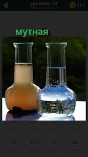 в сосуде стоит мутная вода на столе, другой с прозрачной водой
