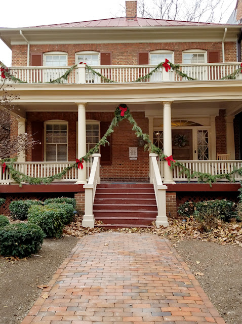 brick house with front porch decorated for Christmas - off center main door.