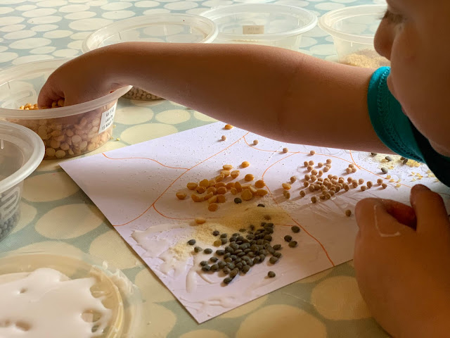 Toddler reaching for more grains to stick on her picture