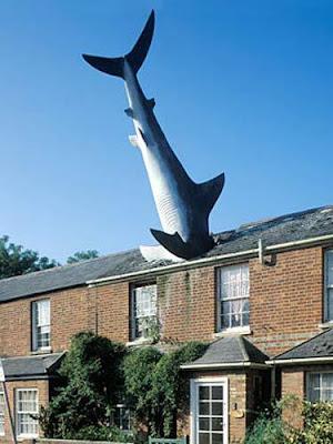 Escultura rara - arte moderna tiburón en el techo de una casa