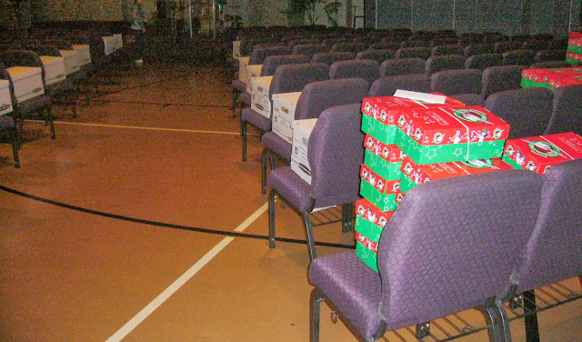Setting up an Operation Christmas Child shoebox packing party in a church sanctuary - gym.