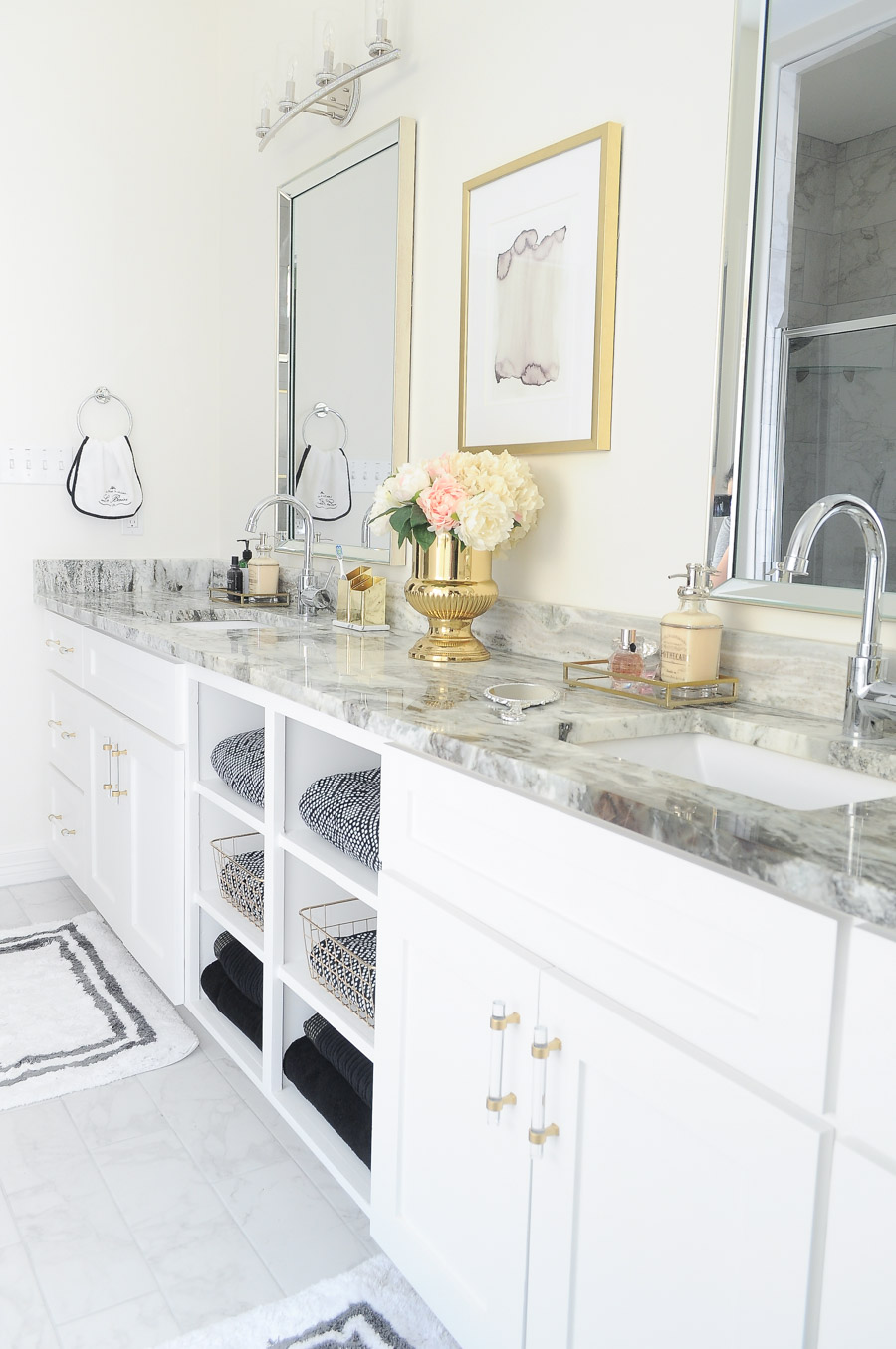 A light and airy bright white and gold master bathroom with black and white decor accents, feminine decor and chic details. This space is swoonworthy!