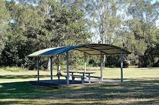 picnic table under a shelter in a park surrounded by green grass and trees