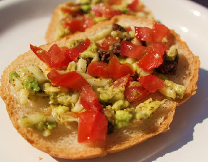 this is a spread that has avocado, tomatoes, olives and mixed into a healthy basil pesto topping a piece of garlic bread
