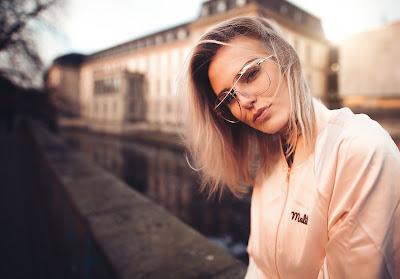 Preciosa chica con gafas y pelo rubio mirando a cámara