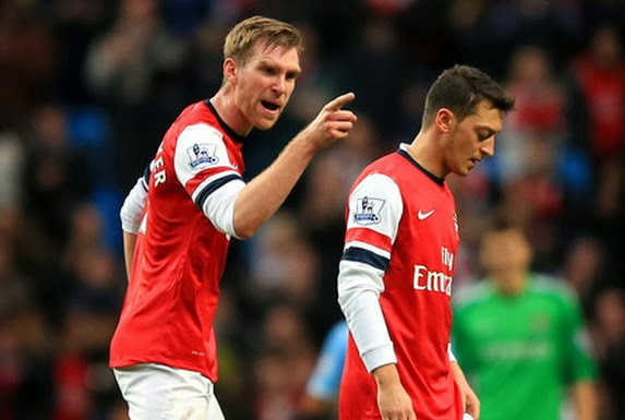 Arsenal's Per Mertesacker has words with teammate Mesut Özil after a match at Manchester City