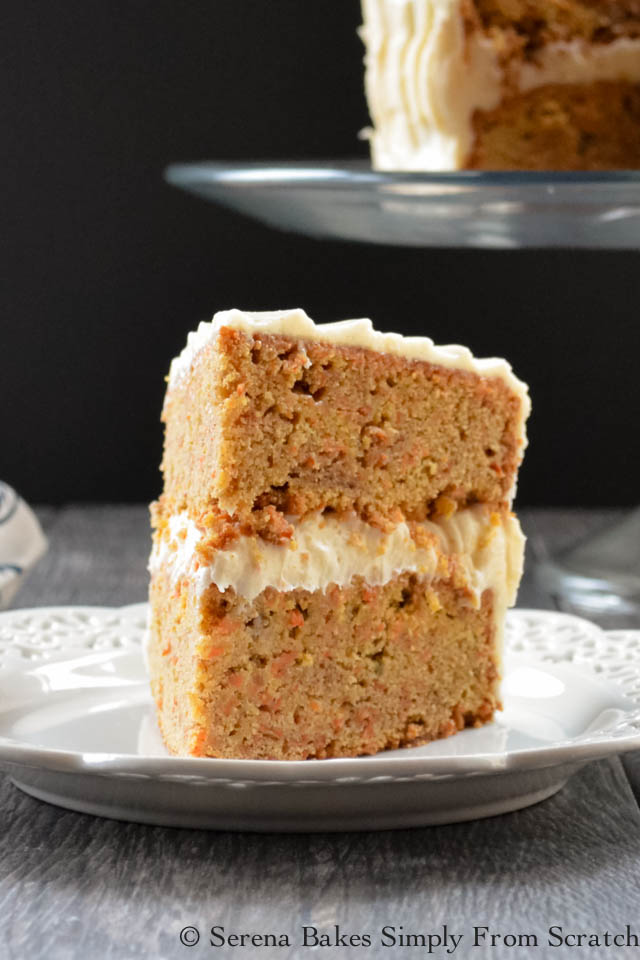 A slice of Carrot Cake with Pineapple Cake with Cream Cheese Frosting on a white plate.