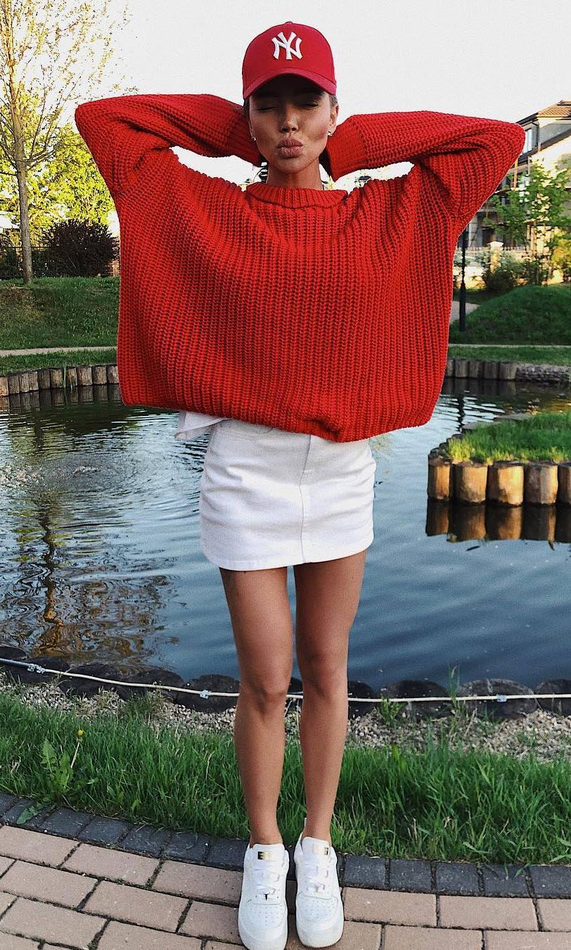 cool fall outfit with a red knit sweaer : hat + white skirt + sneakers