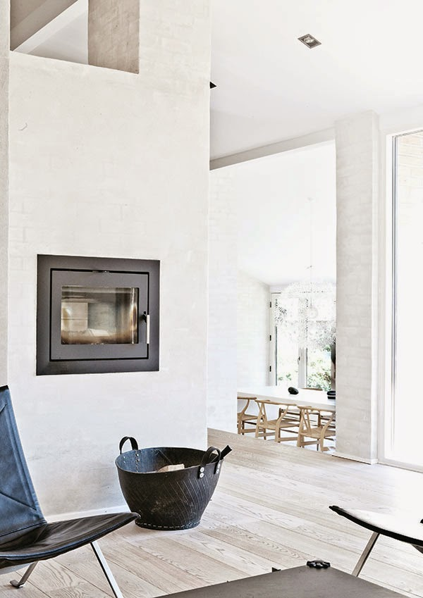 Living room with a modern fireplace in a home by Norm Architects