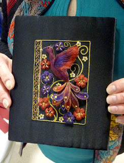 two hands holding a stumpwork project of a red and purple bird with am elaborate tail adorned with gold spangles, surrounded by red, purple and small gold flowers and gold vines