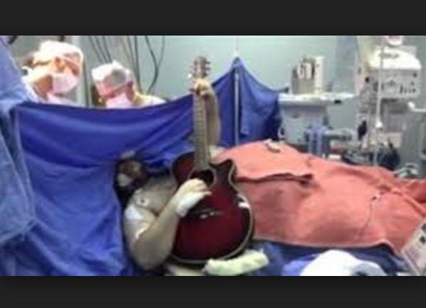 لن تصدق ....مريض يعزف على «الجيتار» أثناء إجراء عملية جراحية في دماغ .... والنتيجة كانت صادمة
