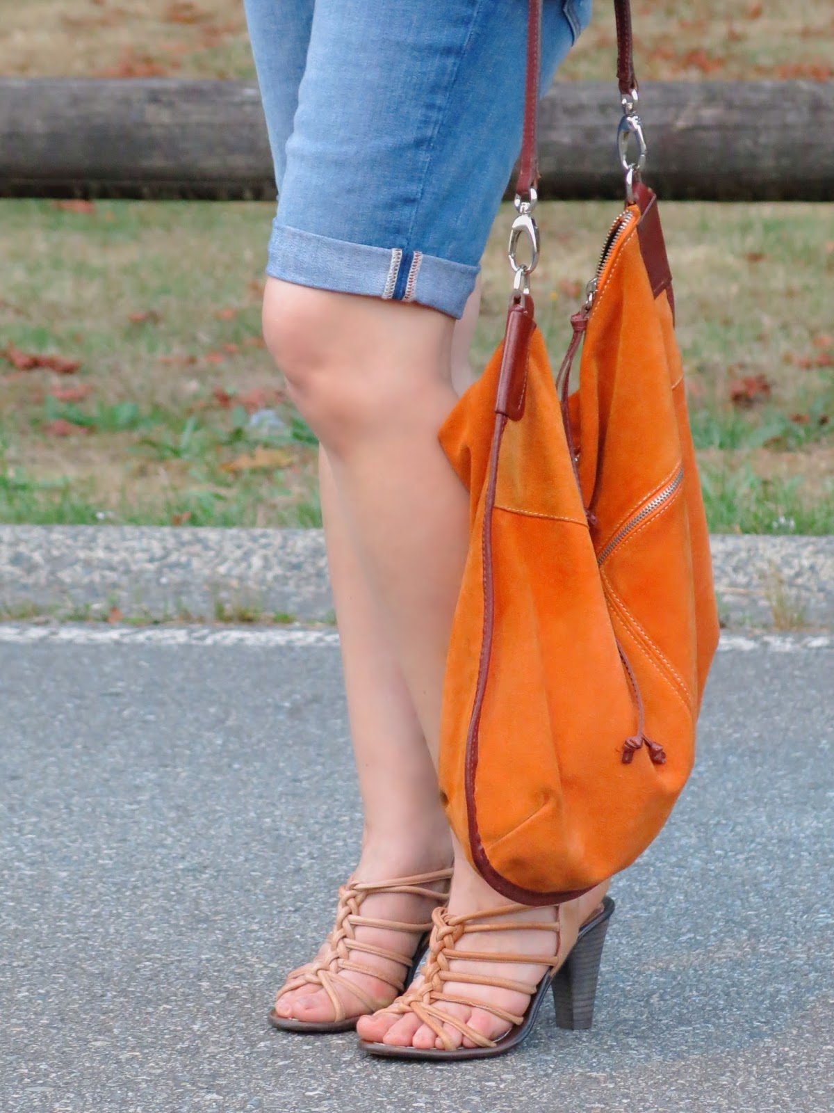 denim bermuda shorts, strappy nude sandals, and an orange suede bag