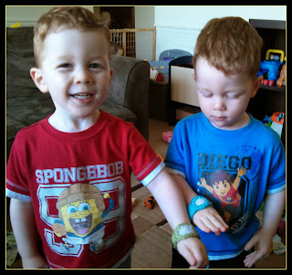 Pictured are two toddlers each showing off crocheted watches. The faces of the watches are white, while one watch band is green and the other is blue.