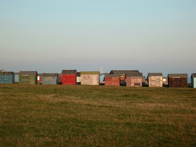 Row of huts at Portland Bill in Dorset. With small wind turbine like a star.