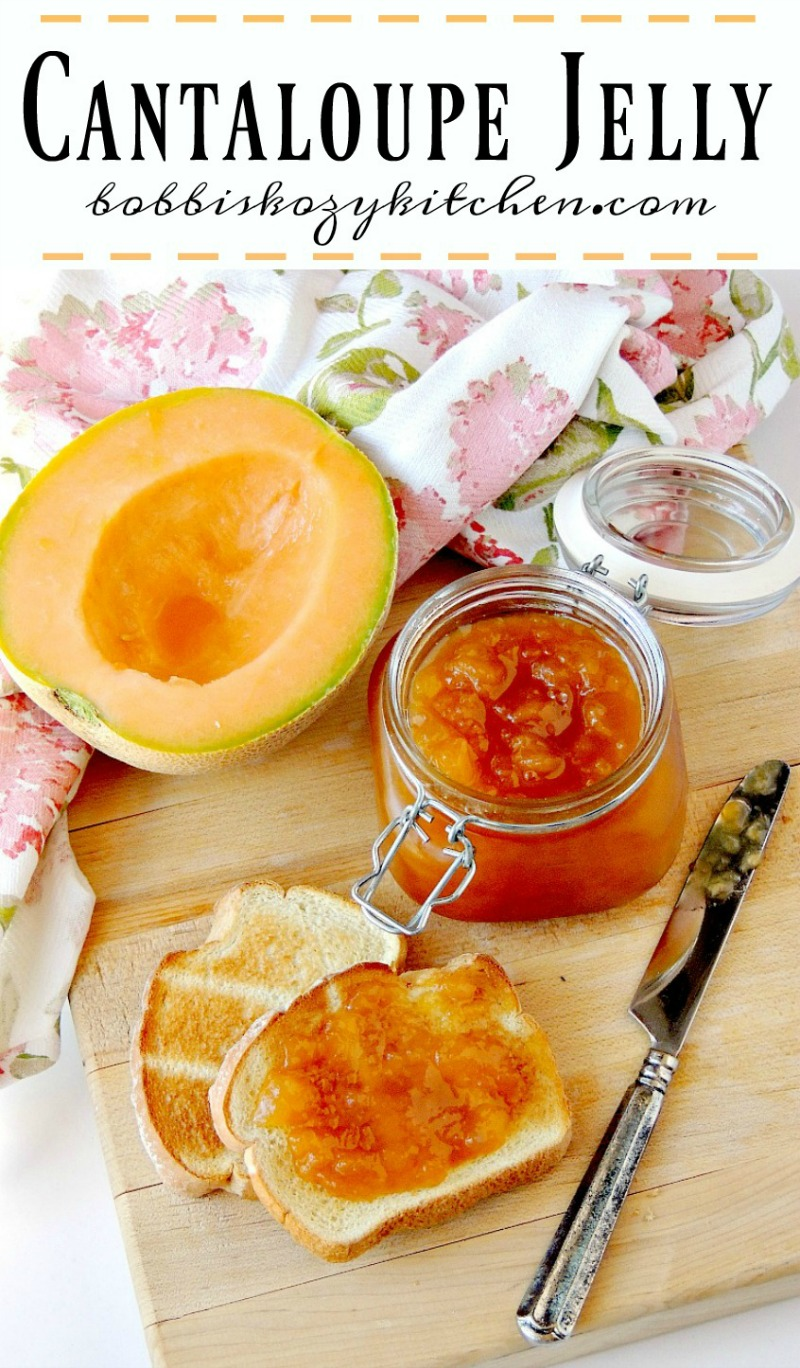 Cantaloupe Jelly in a glass jar with a fresh cantaloupe half and toast beside it on a wooden cutting board with a floral towel.
