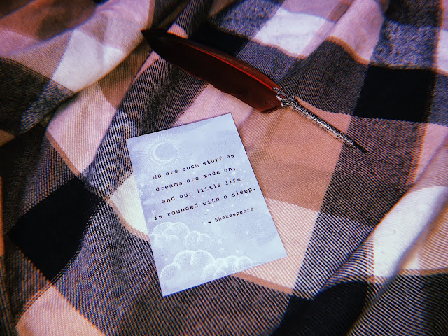 a postcard and feather quill lying on a blanket