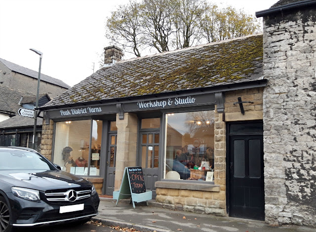 Photo of Peak District Yarns Workshop and Studio from the outside.  An attractive single storey stone building with a moss-covered roof and grey window frames.