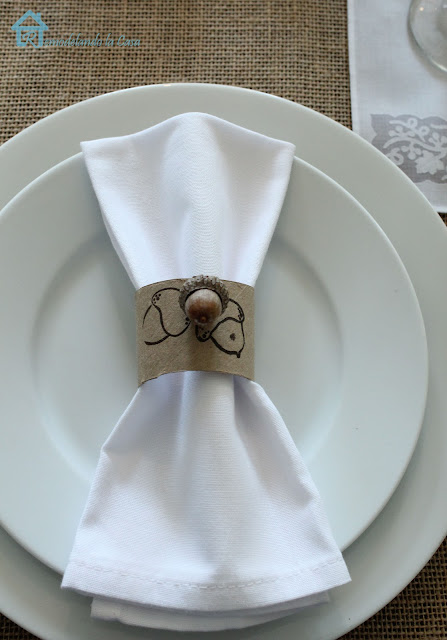 napkin rings with acorn design on white napkin and plates, with a burlap tablecloth