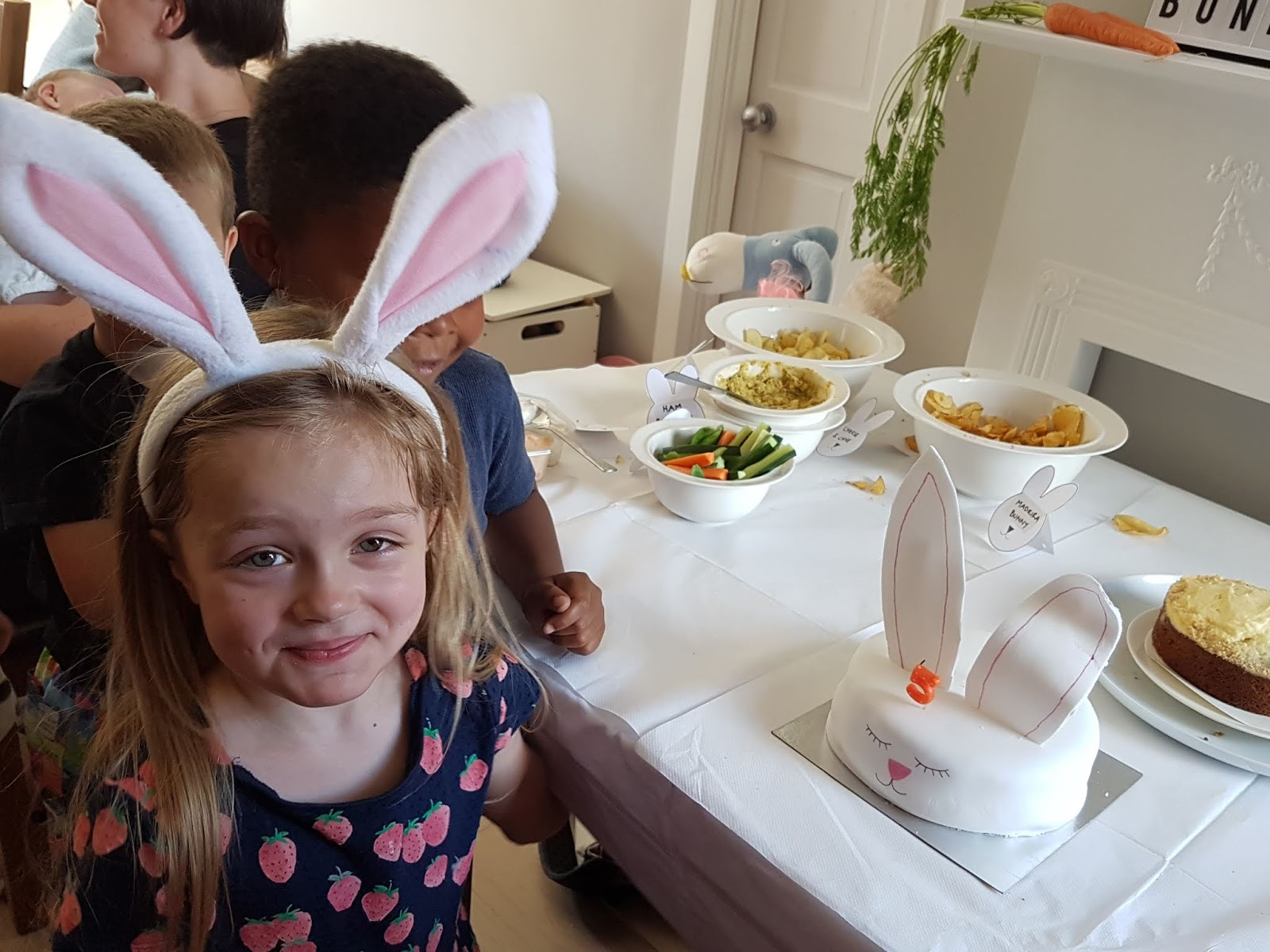 girl in bunny ears with a bunny cake