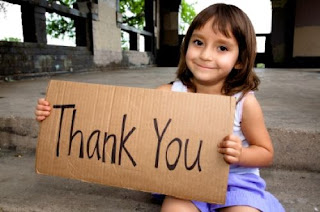Little girl holding cardboard thank you sign.