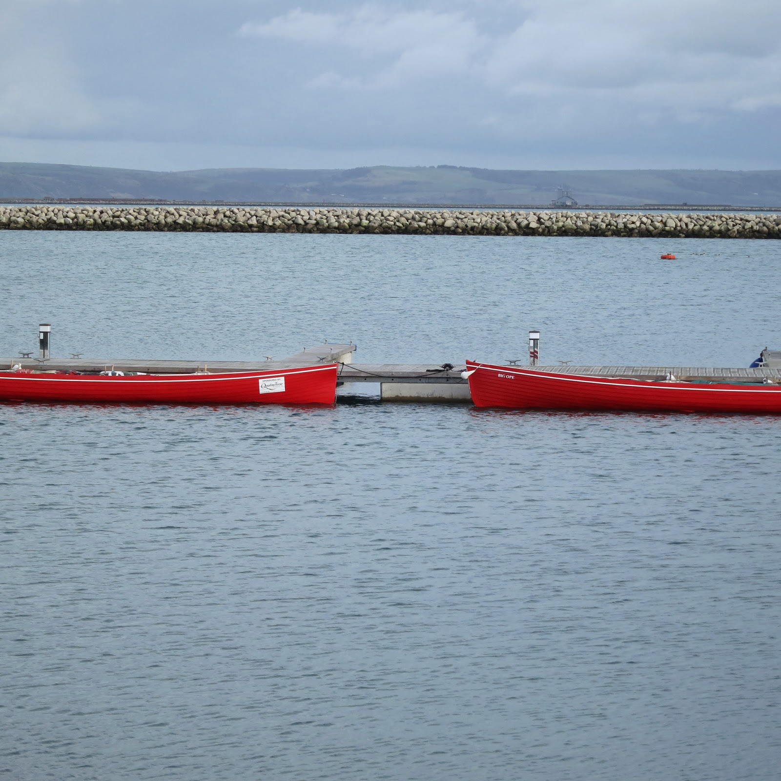 Red canoes facing each other in marina. Portland. Dorset