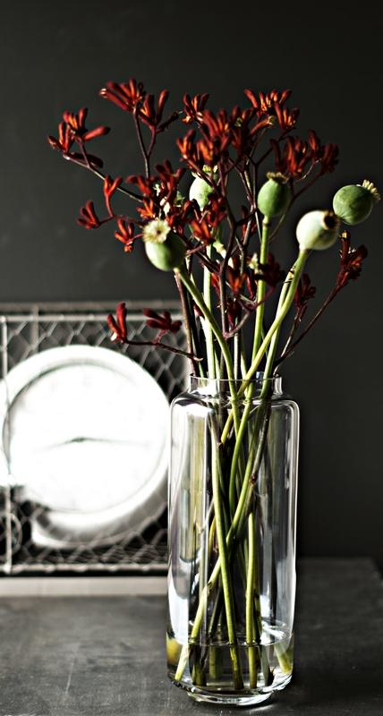 Blog + Fotografie by it's me! - Flower Friday, Mohnkapseln und dunkelrote Blütenzweige mit verschwommener Deko im Hintergrund