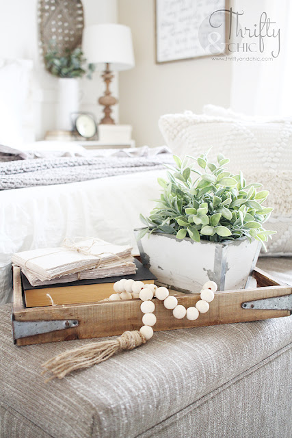 wood bead garland on tray with books and greenery