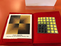 a two page spread with a print of the art work by Victor Vasarely, titled Toll (from the Permutations Series), 1965. There are 4 squares with yellow dots and small square shapes of yellow inside, arranged in a pattern. On the right side is a tactile representation with grey flannel square in the background and buttons in yellow, green, and black sewn in a square pattern