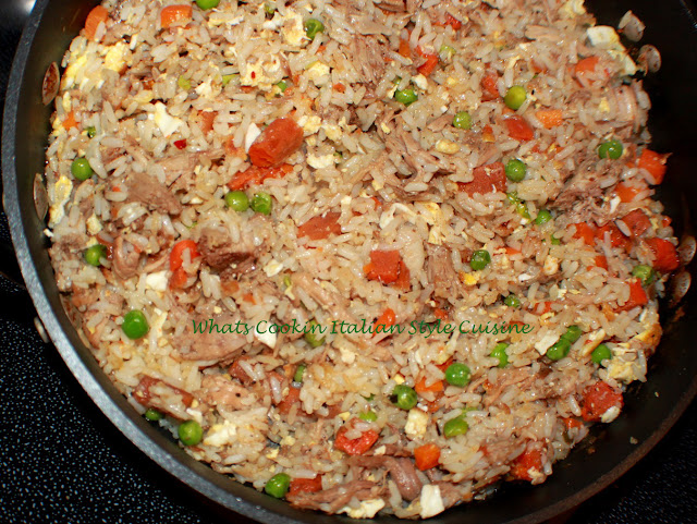 How to make stir fried rice. Asian style rice with peas and carrots with scrambled eggs in a frying pan
