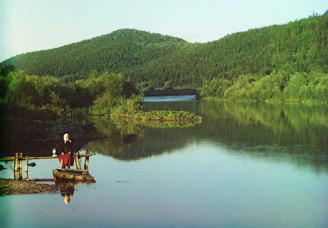 A woman is seated in a calm spot on the Sim River, part of the Volga watershed in 1910.