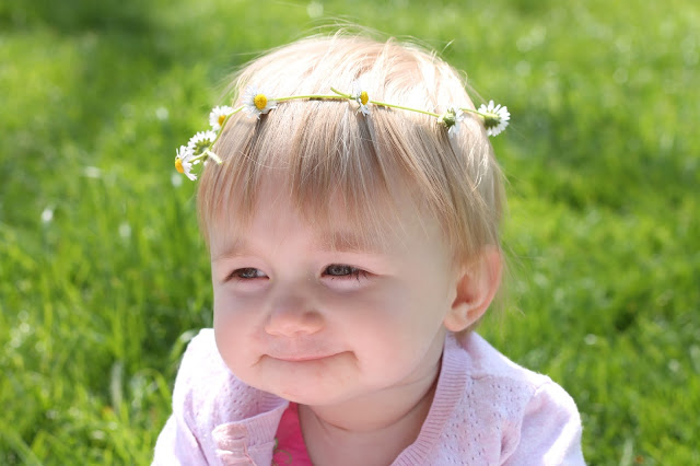 baby girl sat in a field wearing a daisy chain headband