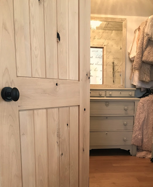 a dresser with stenciled mirror and rustic alder closet door in the master bedroom at Hello Lovely Studio's fixer upper