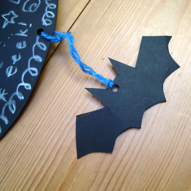 A bat cut out hanging from the brim by wool.